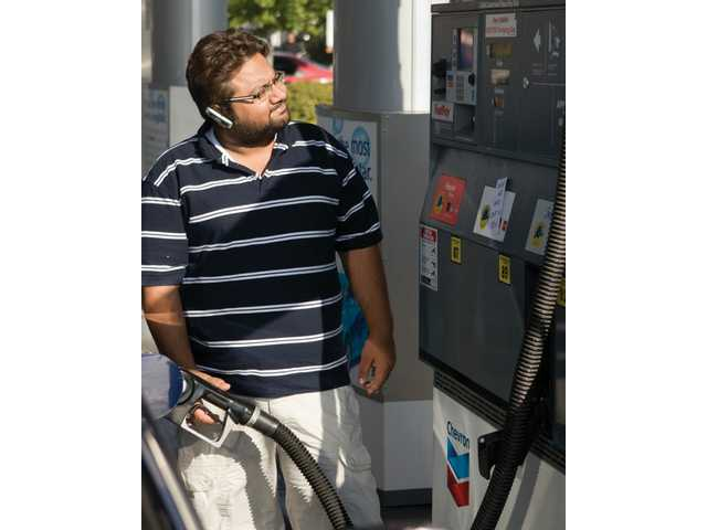 Puneet Saroya watches the dollars quickly rack up on the counter at the Chevron gas station in Santa Clarita on Thursday. His Hyundai Elantra gets 35mpg and costs him $52 to fill up — compared to $35 a tank last year at this time.
