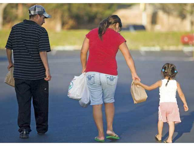 The Romero family carries home food donations from Valencia United Methodist Church on Thursday.