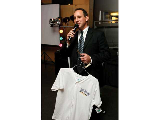 Rabbi Mark Blazer auctions a shirt during a fundraiser for Temple Beth Ami's proposed Jewish Community Center.
