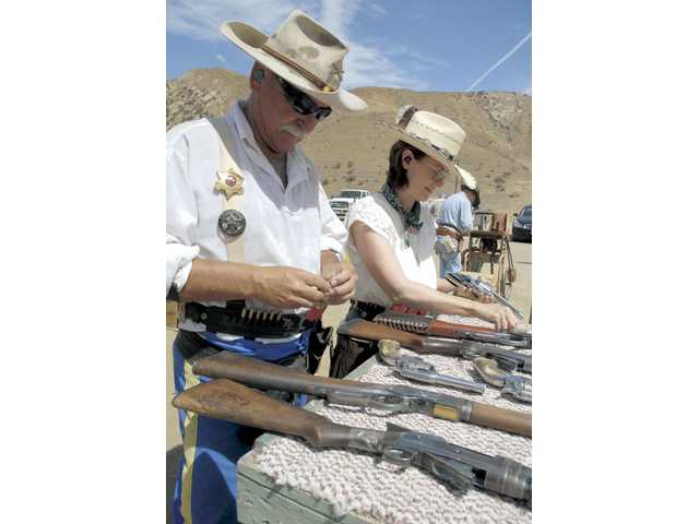 Deadwood Boys President Lefty Longridge (Joe Alecia), left, and Raven Moon (Janice Barnette) prepare shotguns, rifles and pistols as they await their turn to compete at Wes Thompson's Rifle Range in Piru on Saturday.