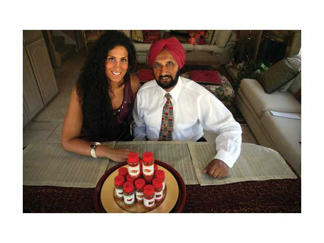 Mohan Sikand, and daughter Gina Sikand in their Valencia home with their family recipe of spice blends to marinate chicken, fish and meats.