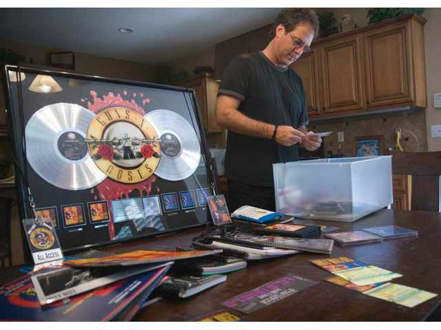 Craig Duswalt, from Stevenson Ranch, organizes his Guns N' Roses memorabilia, which he collected over the years as he toured with the band.