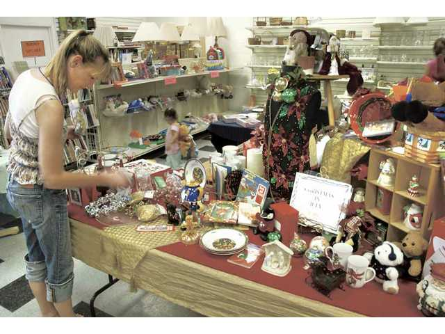 Lynnie Horrigan, of Valencia, looks over the Christmas decorations on sale at the Christmas in July sale at Assistance League Take Two Resale Shop on Saturday.