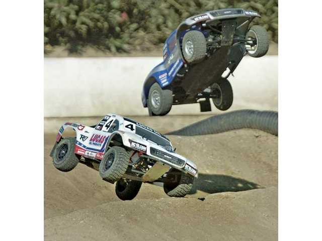 Two trophy trucks crash as they go over a jump in the open short course race at Hot Rod Hobbies and Raceways on Saturday.