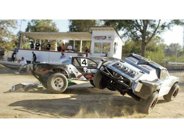 Two 1/8th-scale trophy trucks collide as they careen around a turn in front of the drivers stand at Hot Rod Hobbies and Raceways in Saugus on Saturday.