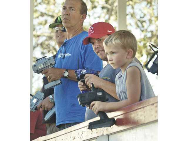 Gabe Hilyard, 6, right, controls his RC car as he competes with older drivers in the open short course race on Saturday.