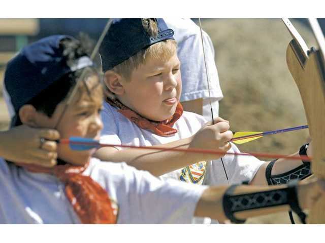 Cub Scouts Mason May, 9, center, Dillon Smith, 8, take aim on the archery range at the Bill Hart District Twilight Camp on Tuesday.