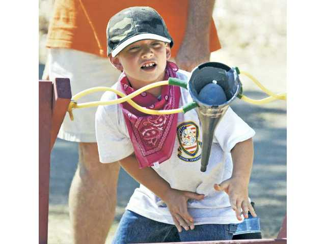Stuart Reyes, 8, launches a water balloon at the opposing team of Cub Scouts at the Bill Hart District Twilight Camp on Tuesday.