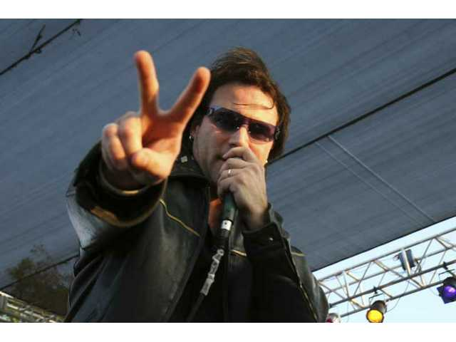 "Hollywood Bono flashes a peace sign during Hollywood U2's performance of ""Beautiful Day"" at Central Park Saturday night."