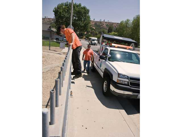 Dan March, front, and Rick Smith, of the city of Santa Clarita's street maintenance crew, inspect the Centurion Way bridge near Saugus High School after Tuesday's earthquake.