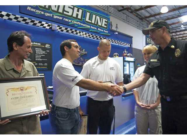 From left, Racer's Edge Indoor Karting owner John Basso, employees Brett Shields, Garrett Brixon and April Price receive recognition from Battallion Chief Mike Carnes for aiding a customer who suffered cardiac arrest June 9 while racing on a track.