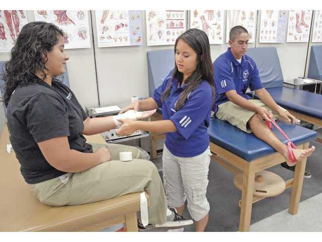 Valencia High School Sports Medicine student trainee Gabi Xerez-Burgos, center, practices a wrist wrap on fellow trainee Marisol Guzman, left, as trainee Adam Tapia practices an ankle rehabilitation Wednesday at Valencia.