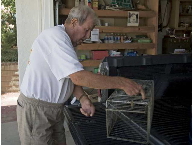Ronald Southwood, 79, unloads a skunk trap from his truck in his Valencia home. Southwood stops skunks from eating from his fruit and vegetable garden with the trap.