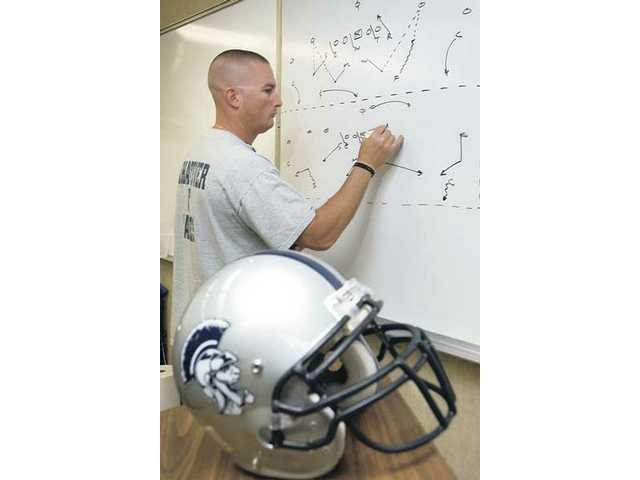 Saugus football head coach Jason Bornn diagrams a play at Saugus High School. Bornn, like some other coaches, spends part of his offseason with programs that employ strategy similar to the Centurions.