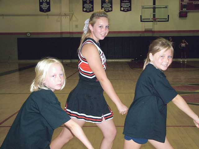 Hart High School varsity cheerleader Alexa Updegraft, center, teaches two girls how to do cheers.
