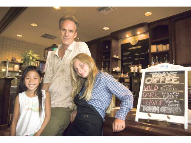 Rick Greenland with his two daughters Leah, 8, left, and Sarah, 11, at Town Grind Coffee Cafe.
