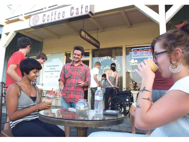 Twenty-year-old Lily Burnett, right, sips on her coffee with Bavani Selvarajah, 19, and William Keegan, 24,  as they hang out outside Town Grind Coffee Cafe in Newhall on Friday.