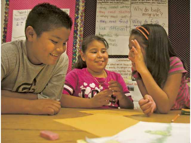 Fourth-graders Oscar Barron, left, Angelica Gonzalez and Chyle Villaceran share information they gathered about puffin birds during a summer school class at Old Orchard Elementary School on Tuesday morning.