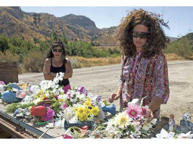 Denise Cruikshank, left, and her sister Mary Logian sift through tributes that were collected and removed  from grave sites by the Eternal Valley Memorial Park staff. The items were set aside in an area  where they could be reclaimed