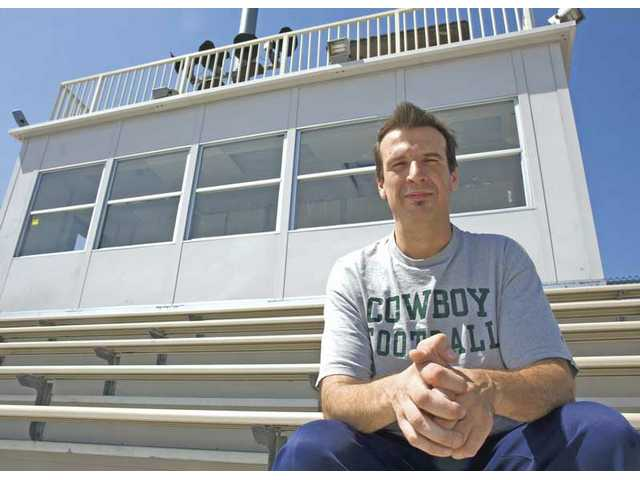 Canyon High public address announcer Mike Civita sits below the press box at  Harry Welch Stadium Thursday. Civita is a 1982 Canyon High graduate who also helps  with tasks for Cowboys football.