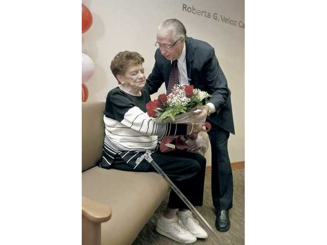 Roberta G. Veloz, left, receives a bouquet of flowers from Roger Seaver, Henry Mayo Newhall Memorial Hospital CEO, at the preview ceremony and tour of the new Roberta G. Veloz Cardiac Cath Lab on Friday. Veloz donated $3 million to the hospital to fund the lab.