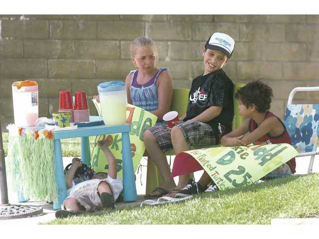 Zach Trujillo, 9, second from right, tries to keep spirits up as his lemonade-selling team relaxes Saturday afternoon. From left, Nick Trujillo, 4, under the table, Micah Dinwiddie, 11, and Tommy Gerges, 9, help Zach raise funds for The Painted Turtle camp for seriously ill children.