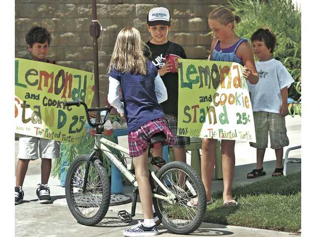 Zach Trujillo, 9, center, sells lemonade to Krista Damann, 11, who passed by on her bike Saturday afternoon. From left, Tommy Gerges, 9, Micah Dinnwiddie, 11, and Nick Trujillo, 4, helped sell lemonade to benefit The Painted Turtle, a camp for seriously ill children in Lake Hughes.