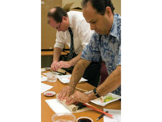 Andy Hetzel, left, and Jose Estrada, both from Valencia, make their first sushi rolls at Let's Make Sushi! at College of the Canyons on Thursday. Executive Chef Avery Roemer instructed nine people in the one-time night class on the basics of making a California Roll as well as several other popular rolls.