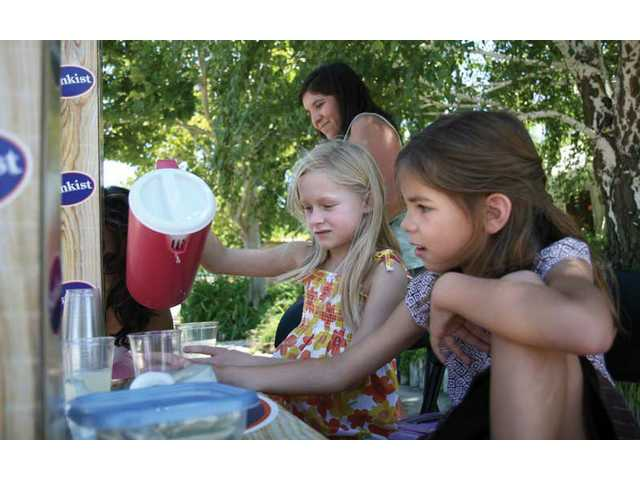 Paige Chabot, 8, pours lemonade in a cup as friend Taylor Beckham, 7, watches on Saturday afternoon at the corner of Paragon Street and Santa Clarita Road.