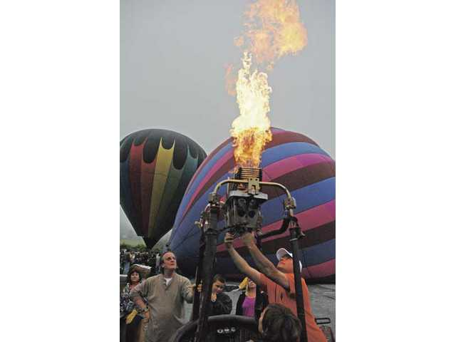 Don Oswald, right, conducts a propane test before raising his hot-air balloon at the Citrus Classic Festival in Santa Paula on Saturday.