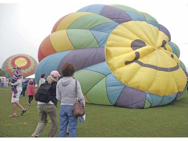 Spectators from all over southern California wander freely between balloons as they are inflated with hot air at the Citrus Classic Festival in Santa Paula on Saturday.