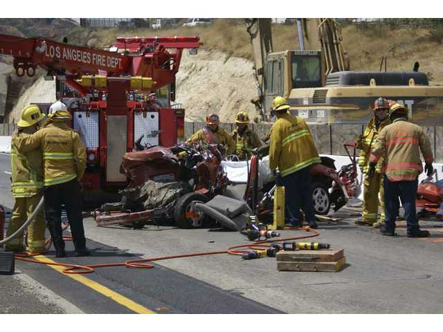 As one L.A. County fireman appears to console another at left, a crew covers the body of a woman killed when her Dodge Neon collided with a Ford F-350 truck on Interstate 5 in the Newhall Pass early Monday afternoon.