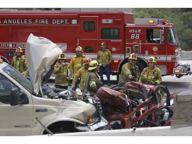 L.A. County emergency crews and California Highway Patrol officers prepare to remove the body of a woman killed when her Dodge Neon collided with a Ford F-350 truck on Interstate 5 in the Newhall Pass early Monday afternoon.
