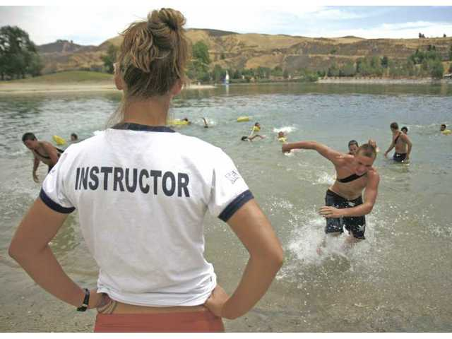 Lifeguard instructor Kayla Worden watches as the junior lifeguards practice on Tuesday for the rescue race event they will participate in during the Junior Lifeguard Competition at Castaic Lake.