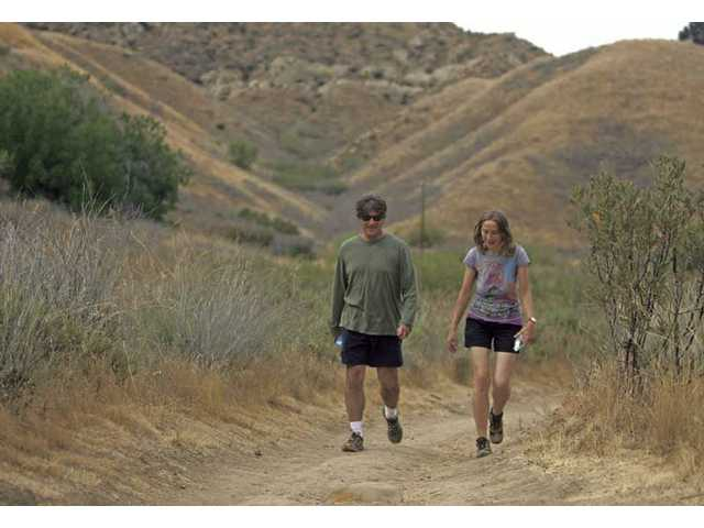 Robert Lobato, 49, of Valencia, hikes with a friend on the 5.1-mile Towsley View loop at Ed Davis Park in Towsley Canyon Santa Clarita Woodlands Park on Monday afternoon. The two are currently training for a six-hour hike they will participate in near Pismo Beach.