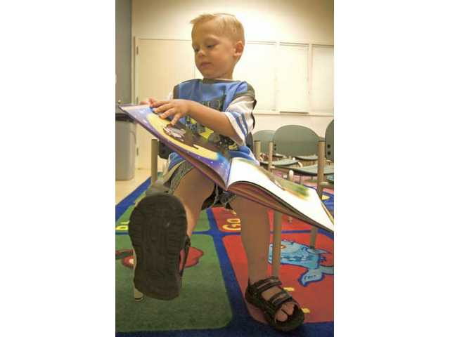 "Three-year-old Andy Clark reads his favorite book, ""The Magically Mysterious Adventures of Noelle the Bulldog,"" written by Gloria Estefan, during the Storytime Adventures program at the Santa Clarita Activities Center on Monday morning."