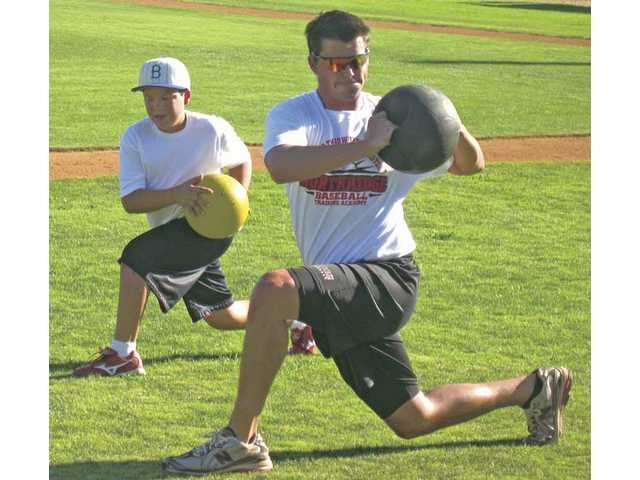 Youth baseball player Nicko Franco, left, trains with  Cal State Northridge baseball player Jason Dabbs in Northridge earlier this month.