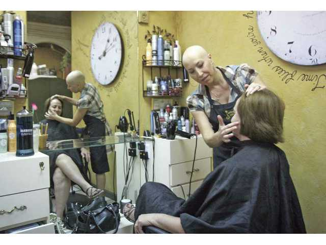 Roselund styles the hair of longtime customer Linda Johnson on Tuesday.
