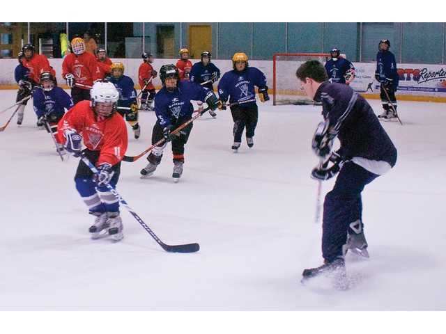 Kids participate in the first hockey camp on Monday at the Valencia Ice Station with one of their coaches from the Valencia Flyers.