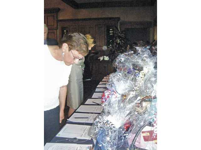 Debra Blemker, a five-year cancer survivor, surveys the silent auction items on display.