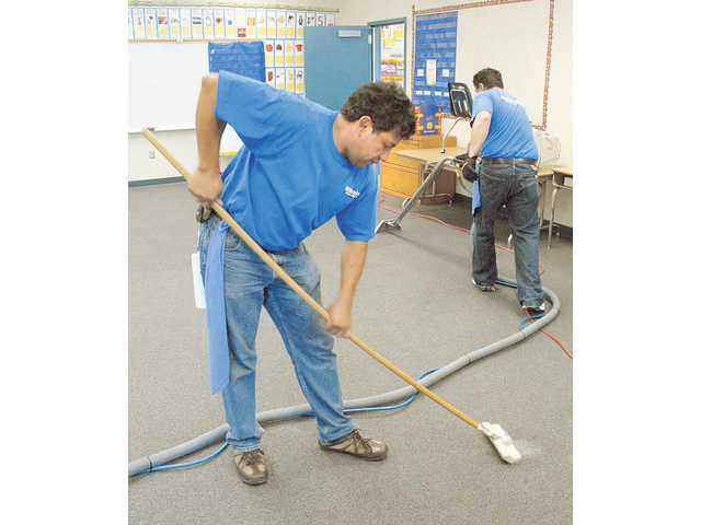 "Rojello Rosas, left, does a spot cleaning as Eric Gonzalez uses a hot-water system to clean the carpets in one of 39 classrooms that Millenium Maintenance Systems cleaned for free at Rosedell Elementary School on Thursday. The cleaning company donated time and work to clean up the school's campus as a  ""thank you,"" because the owner's daughters attended the school. The service is estimated to be worth at least a $2,000."