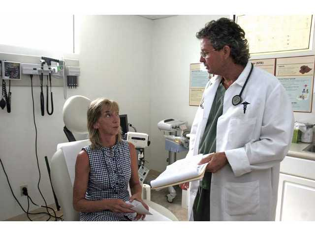 Physician assistant Michael Gales, right, at the Samuel Dixon Family Health Centers, Inc. in Val Verde reviews paperwork with patient Catherine Cornell on Wednesday. The center, along with two other centers in the Santa Clarita Valley, will have to cut its budget drastically since it will not recieve any help from the federal stimulus money.