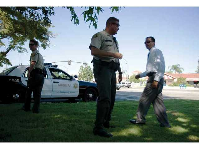 Sheriff's deputies and detectives converse outside the Santa Clarita Valley Civic Center in Valencia after taking a check forgery suspect into custody Thursday afternoon.