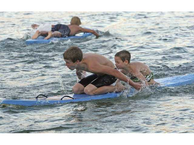 Grant Wolf, 13, uses teamwork with his brother Chapman, 6, during the paddle race. Junior lifeguards ages 9 to 17 invited friends and family to compete at the lake to celebrate the completion of their summer training program.