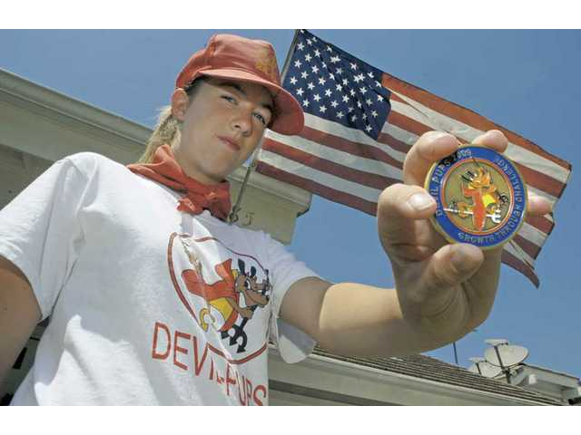 Josephine Behrens displays the medallion she received from the U.S. Marines after completing her Devil Pups training camp. The exclusive 10-day program for teens mimics the rough and spartan Marine life and emphasizes physical fitness and discipline.
