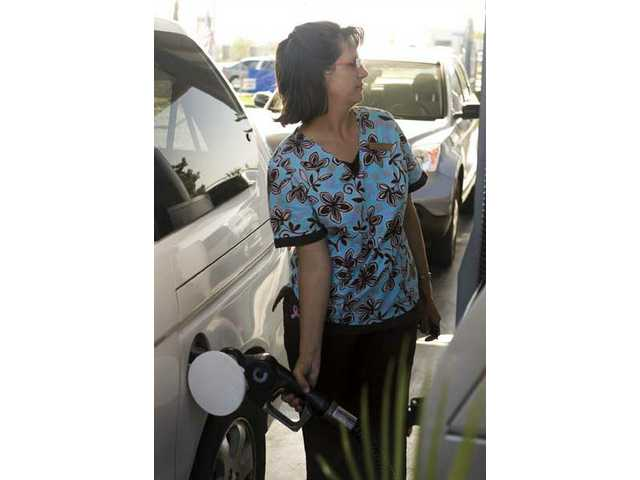 Rebecca Gafner fills up her Honda Odyssey in Santa Clarita during late July. Her Odyssey gets 25 miles per gallon, and she spends an average of $60-$70 per week driving her two children to school and going to work.