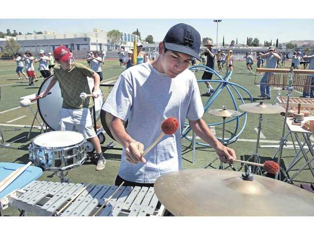 "Saugus High School junior Steven Widlman, right, plays the xylophone and cymbals as senior Travis Mays plays the bass drum and gong in the ""pit"" of the percussion section during the marching band's hell week on Friday."