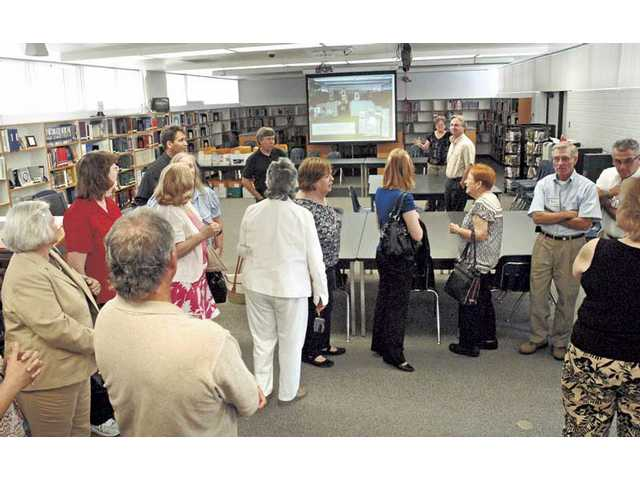 District officials tour the newly modernized library media center at Placerita Junior High on Tuesday.