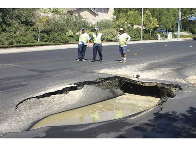 Workers from Valencia Water Company look at the sinkhole in the middle of Decoro Drive on Sunday afternoon.
