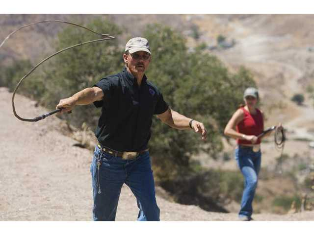 Anthony De Longis, from Canyon Country, shows off his lasso skills at his ranch home as wife Mary De Longis watches from behind on Sunday afternoon.